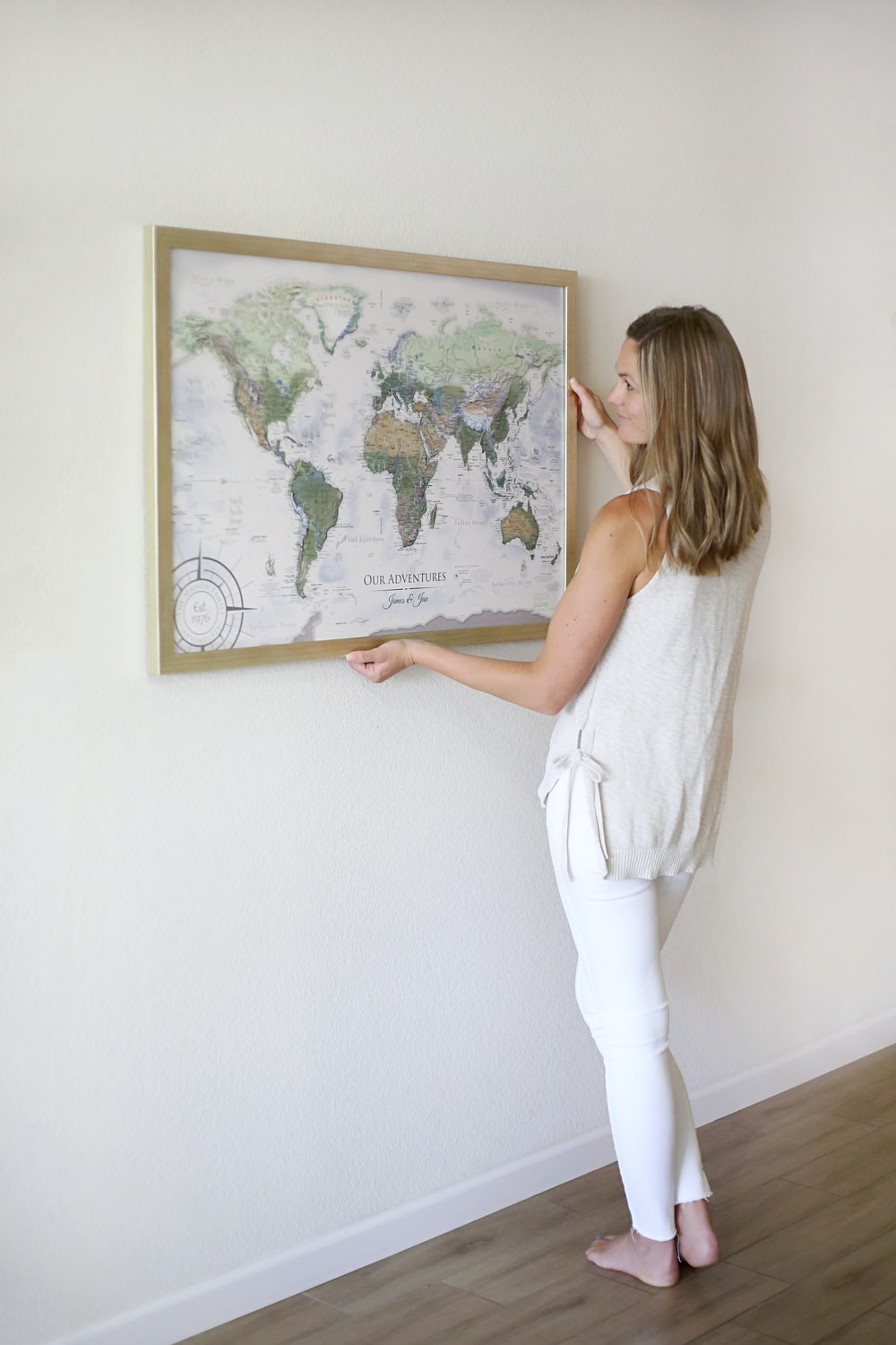 woman in white tank top and white pants standing in front of map