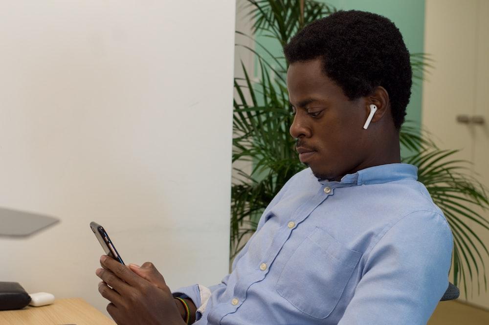 man in blue dress shirt holding smartphone