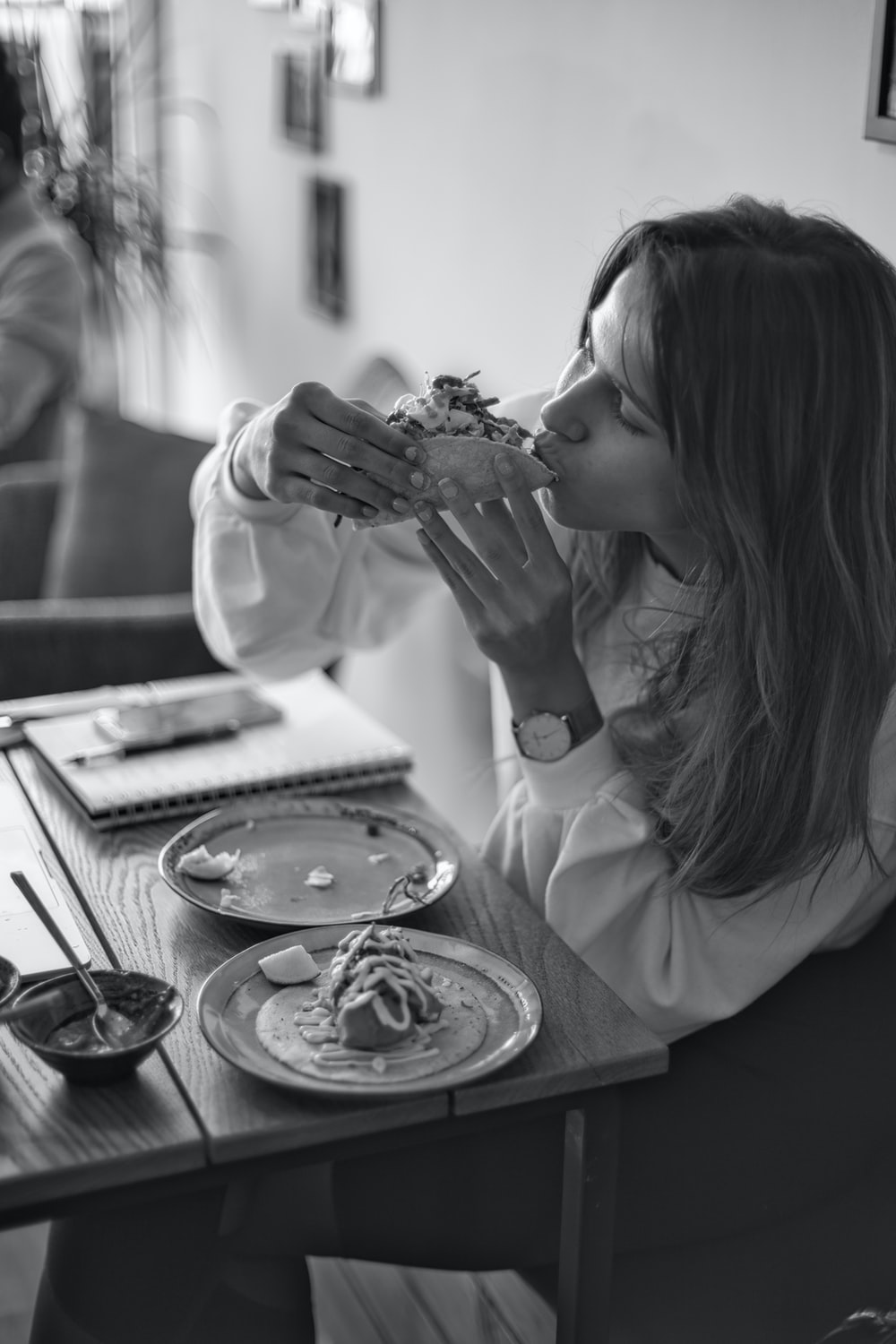 grayscale photo of woman eating