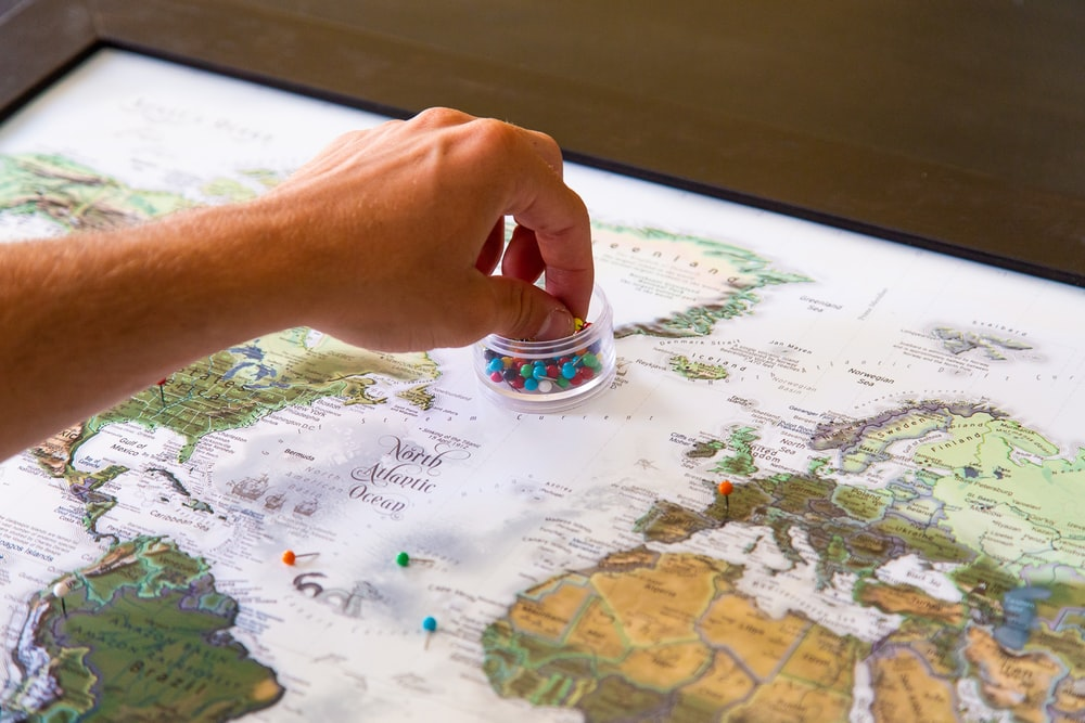 person holding silver ring on white and blue map