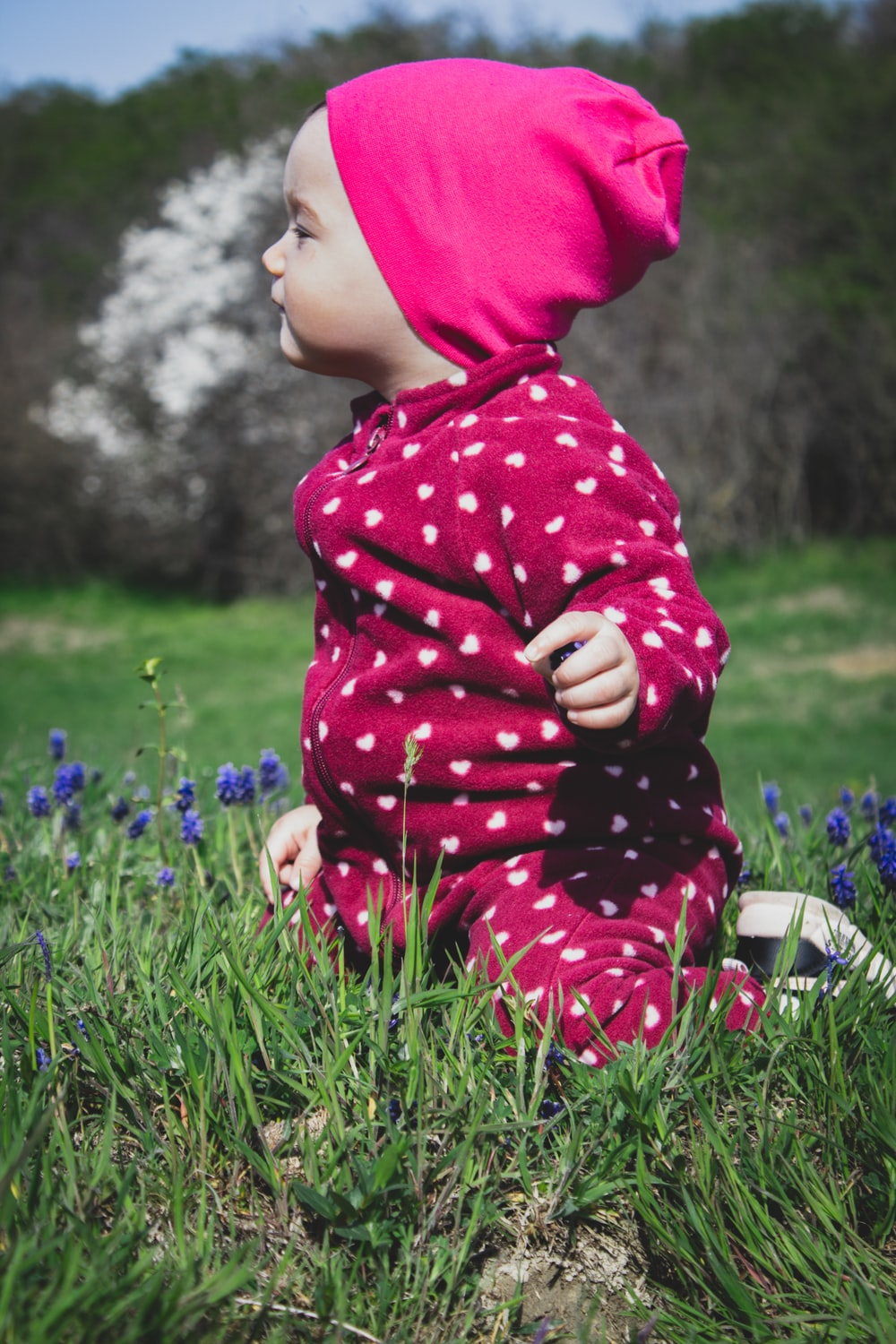 girl in red and white polka dot hoodie sitting on green grass field during daytime