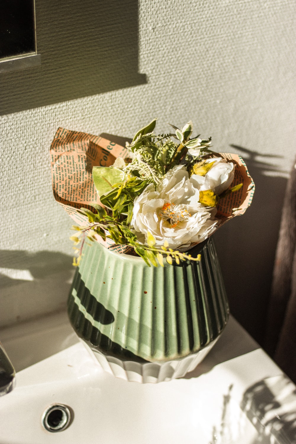 white and yellow flower bouquet in green and white striped vase