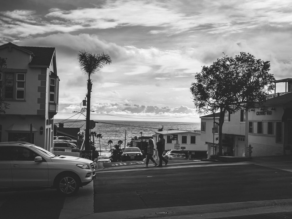 grayscale photo of people walking on sidewalk near cars and buildings