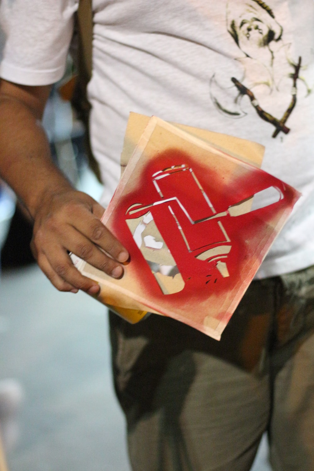 person holding white and red plastic pack