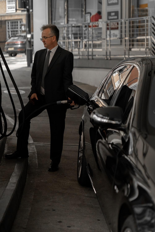 man in black suit standing beside black car