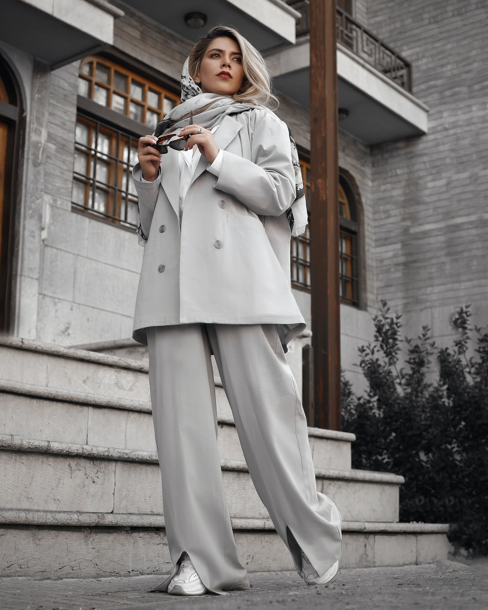 woman in white coat and pants standing on stairs