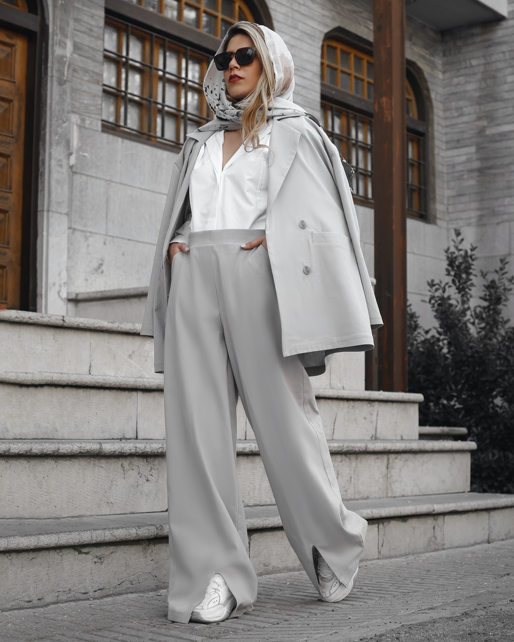 woman in white coat standing on gray concrete stairs