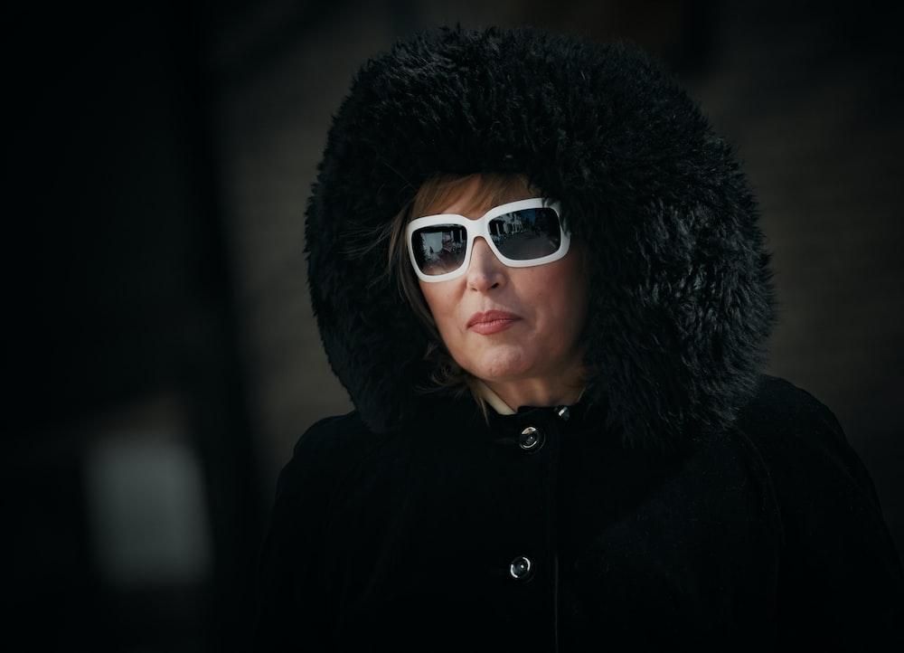 woman in black fur coat wearing black sunglasses