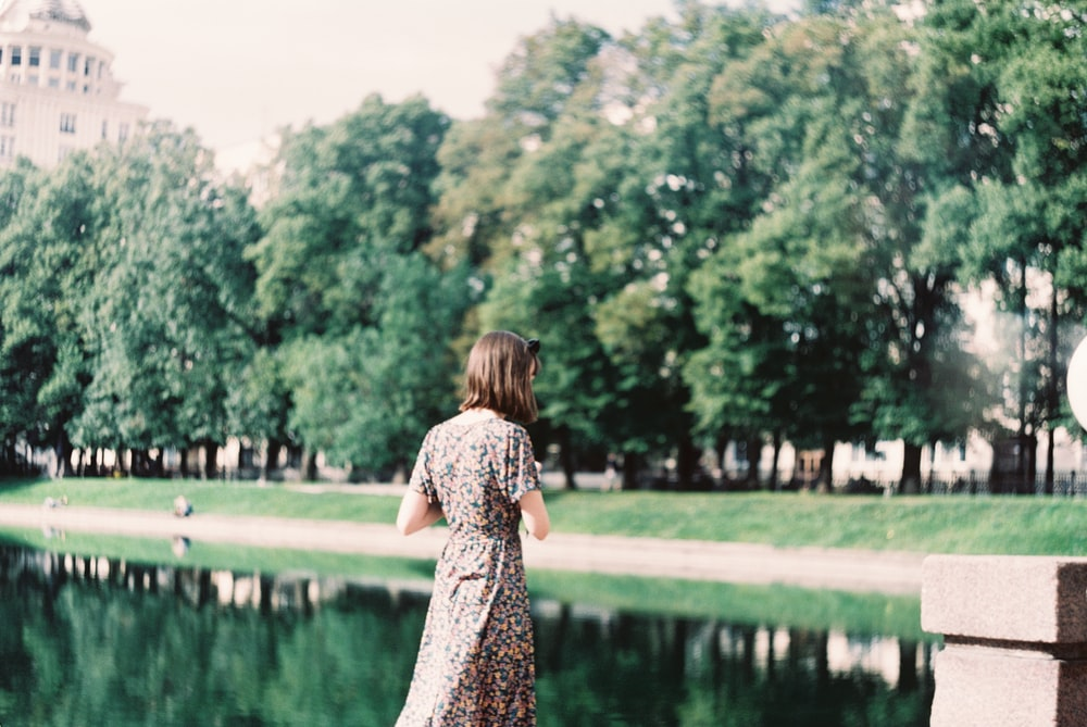 woman in black and white floral dress standing near green grass field and body of water