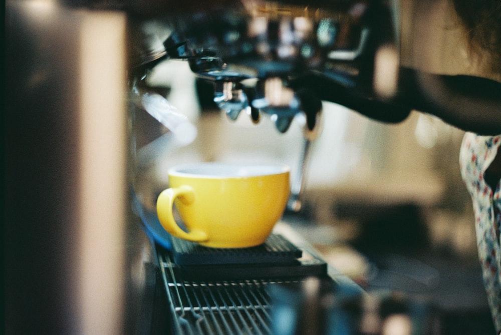yellow ceramic mug on black and silver espresso machine
