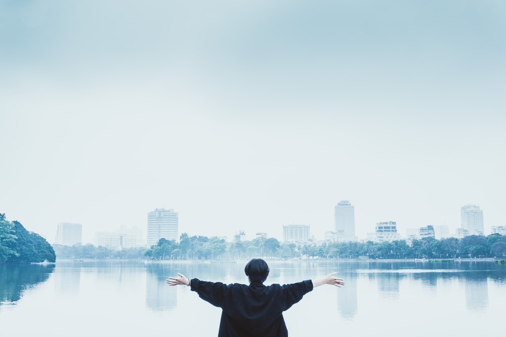 man in black jacket standing near body of water during daytime