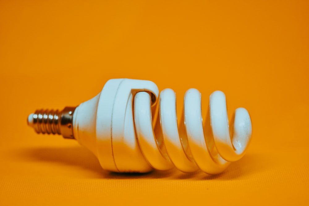 white spiral light bulb on yellow surface
