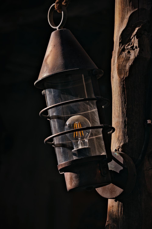 black metal candle lantern on brown tree trunk
