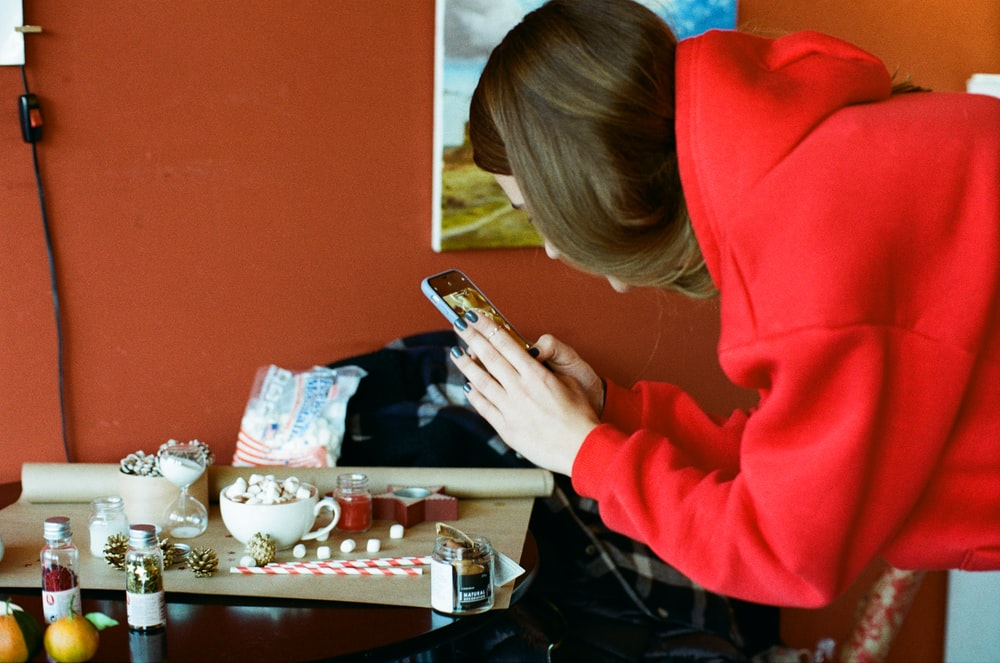 woman in red hoodie using smartphone