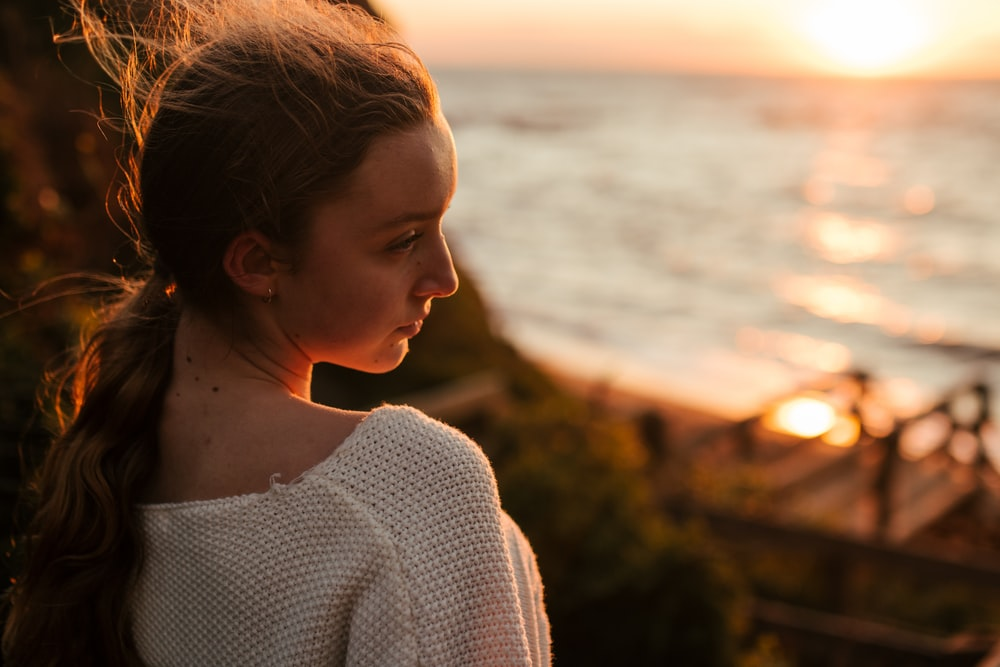 woman in white knit sweater standing near body of water during daytime