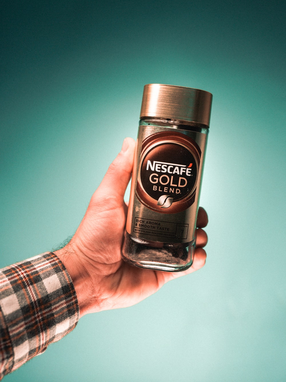 person holding nescafe gold blend bottle