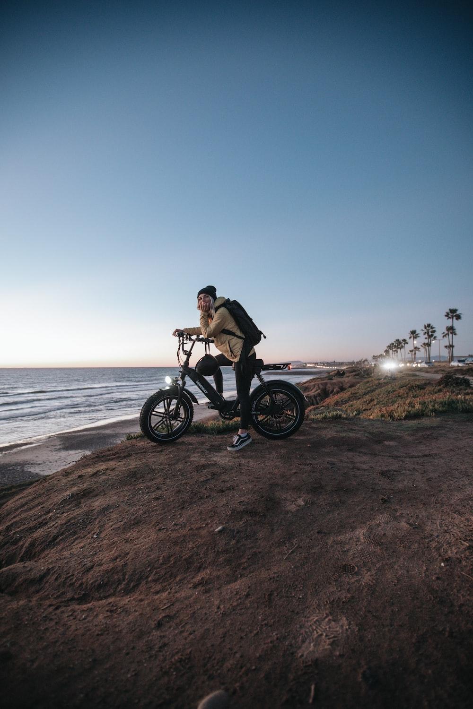 man in black jacket riding on black motorcycle near sea during daytime
