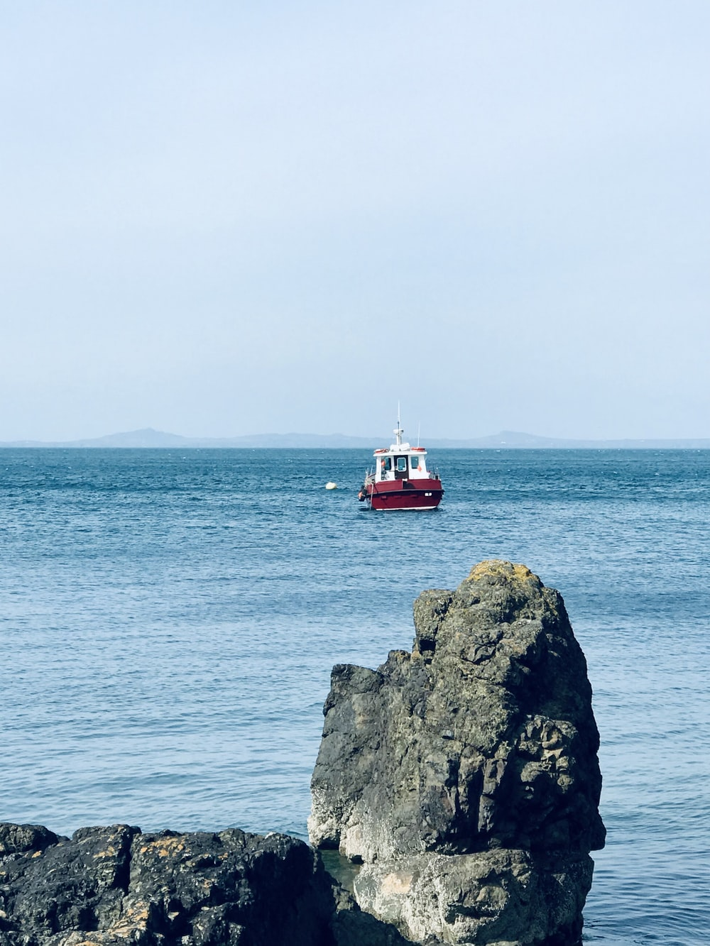 red and white boat on sea near gray rock formation during daytime