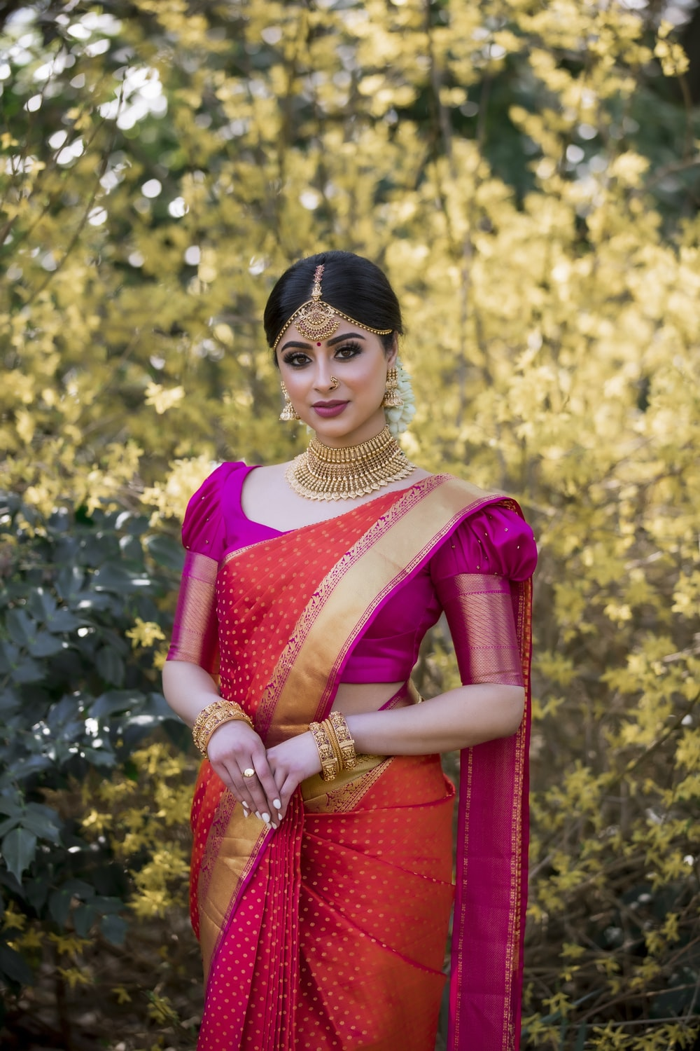 woman in red and white sari standing near green trees during daytime