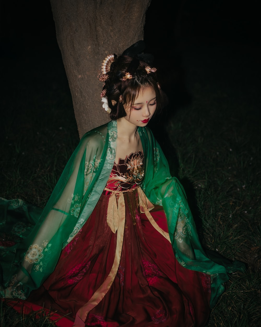 woman in green and red dress sitting on tree trunk