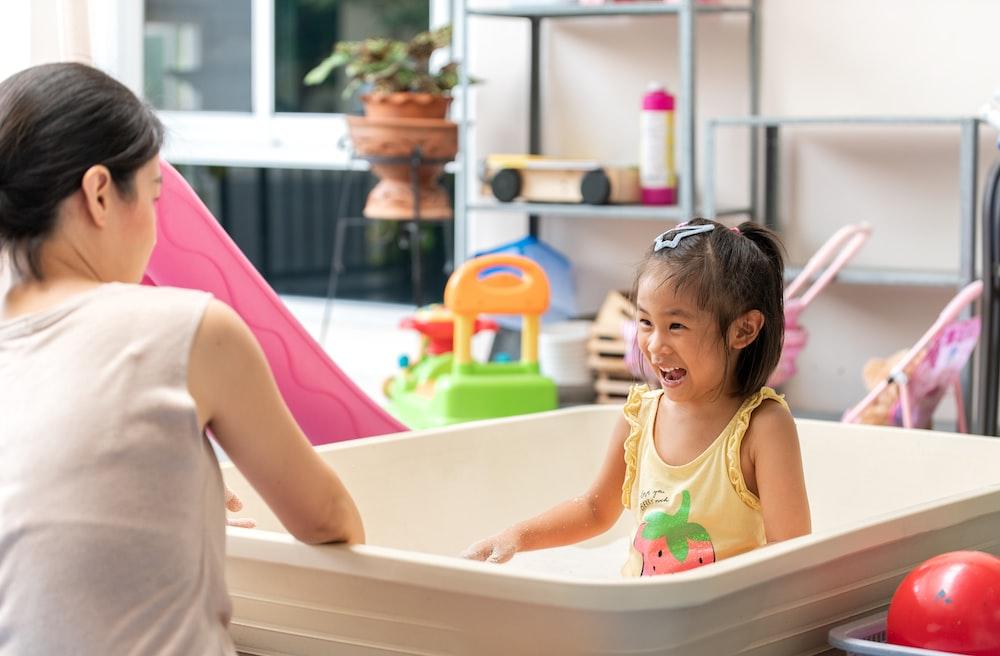 girl in pink tank top sitting on white bathtub
