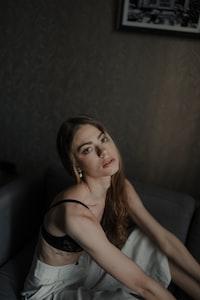 woman in black brassiere lying on bed