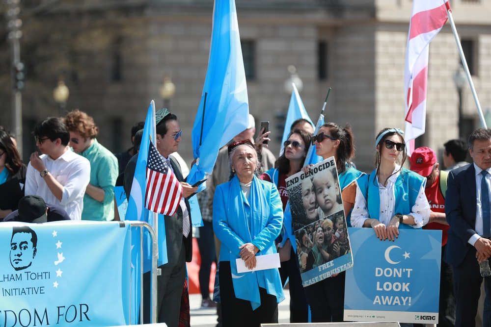 woman in blue long sleeve shirt holding blue flag