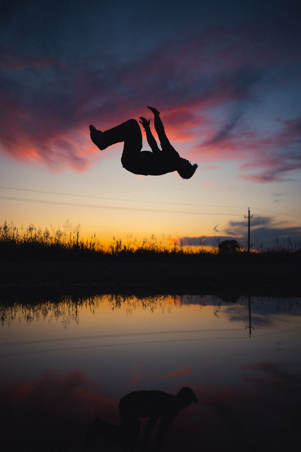 silhouette of person jumping on water during sunset