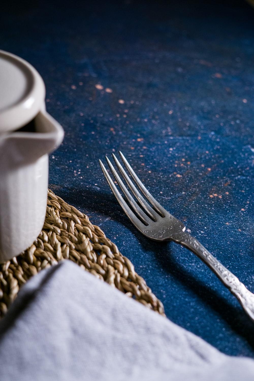 silver fork beside white ceramic mug