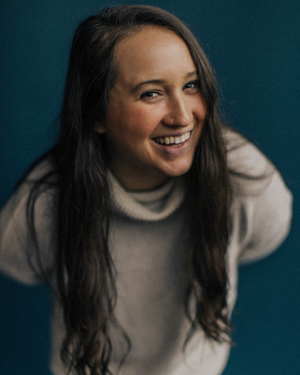 smiling woman in white turtleneck sweater