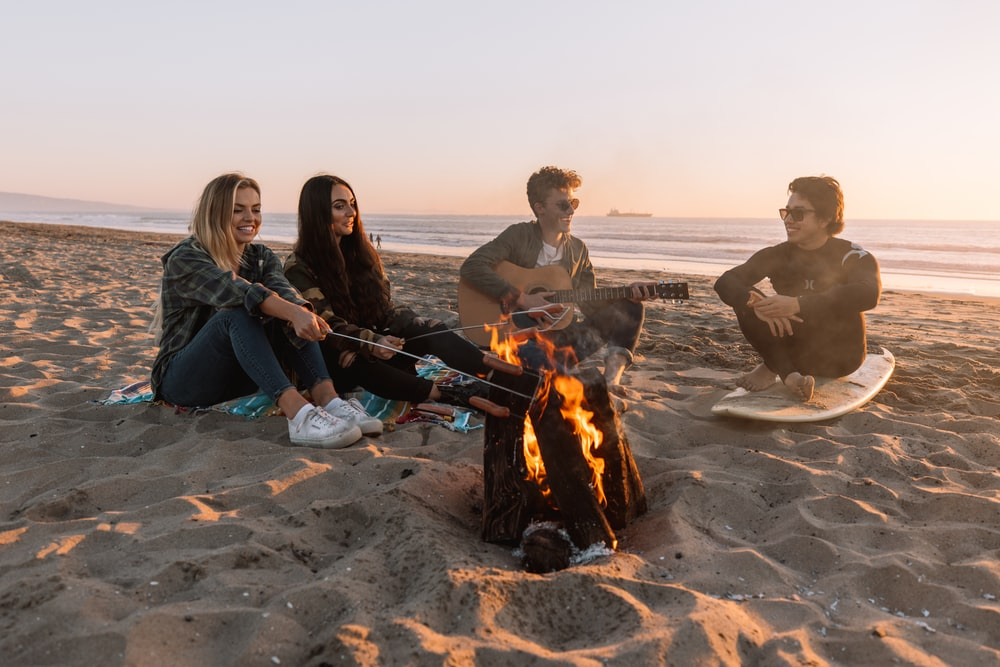 man and woman sitting on sand near bonfire during daytime