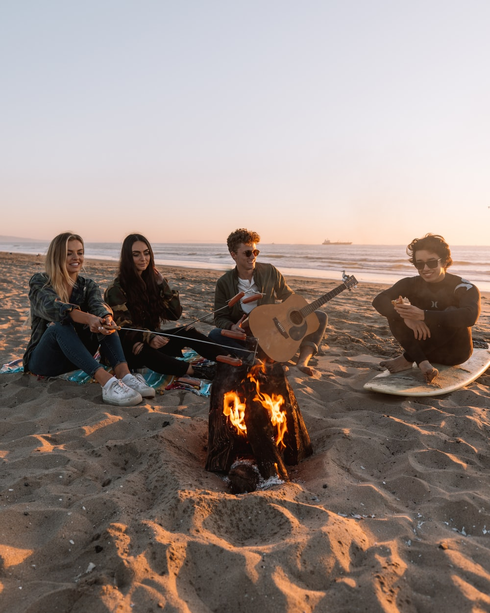 people sitting on sand near bonfire during daytime