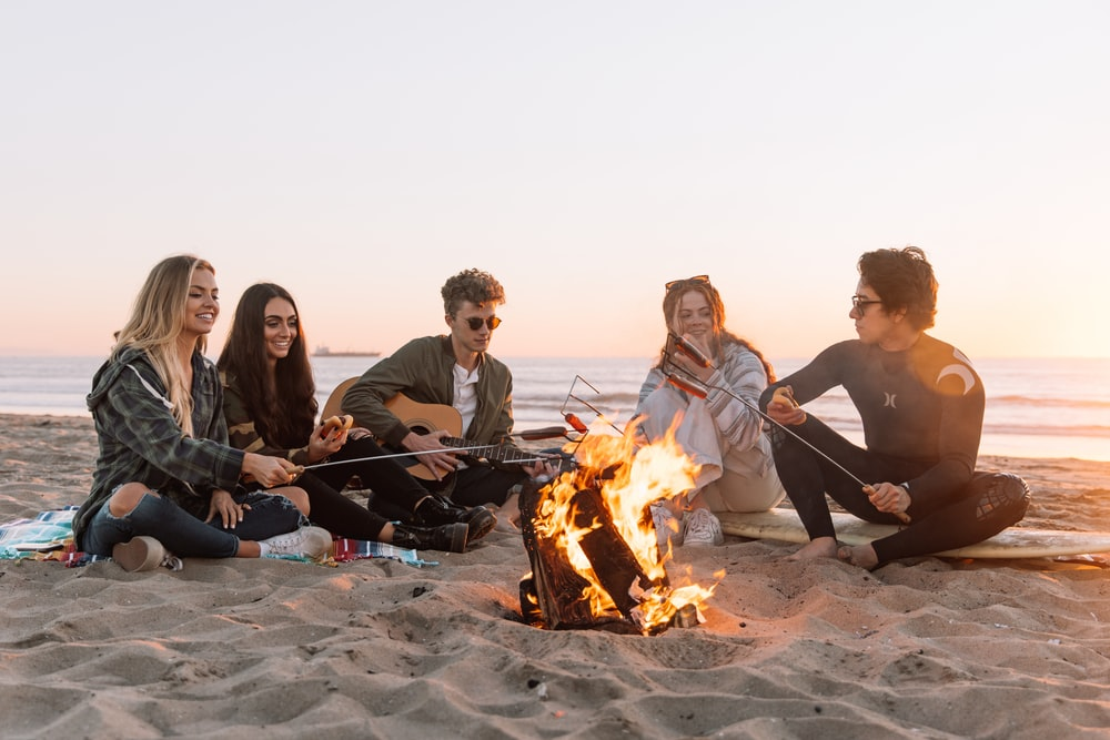 group of people sitting on ground with bonfire during daytime