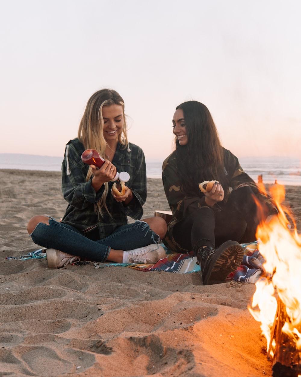 3 women sitting on brown sand near bonfire during daytime