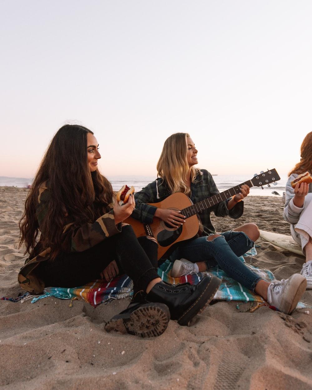 3 women sitting on brown sand playing guitars during daytime