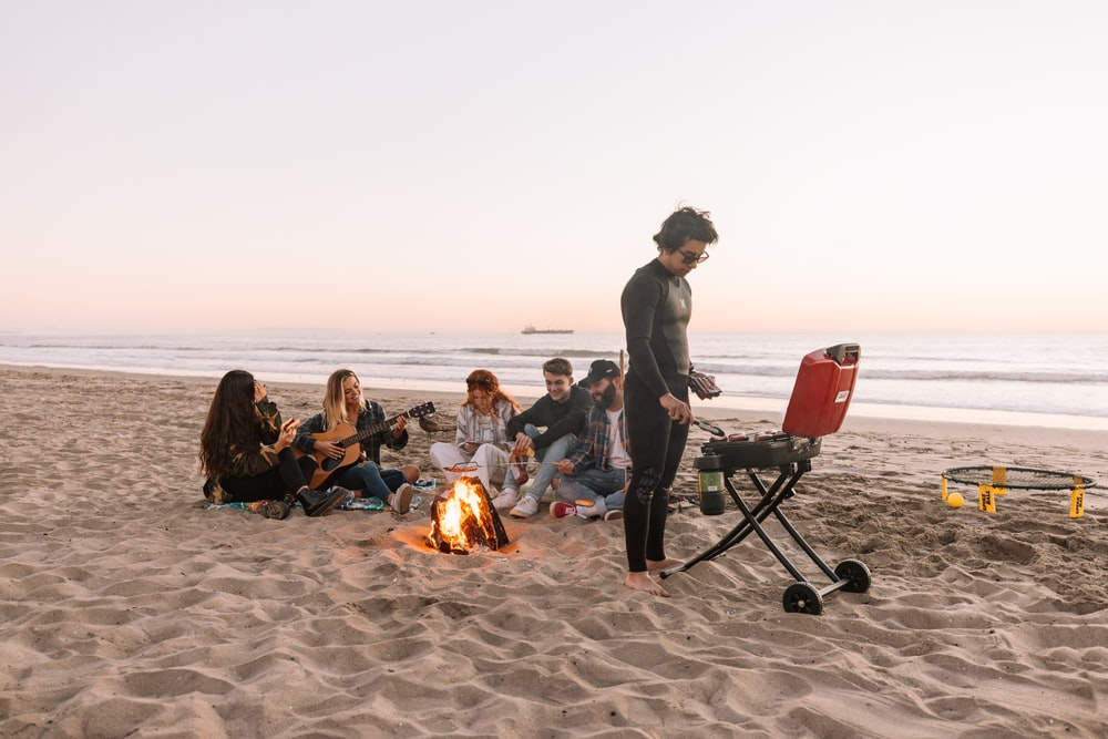 people sitting on camping chairs on beach during daytime
