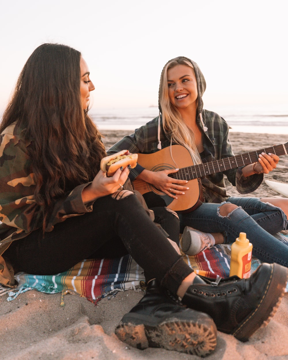 2 women sitting on the ground playing acoustic guitar