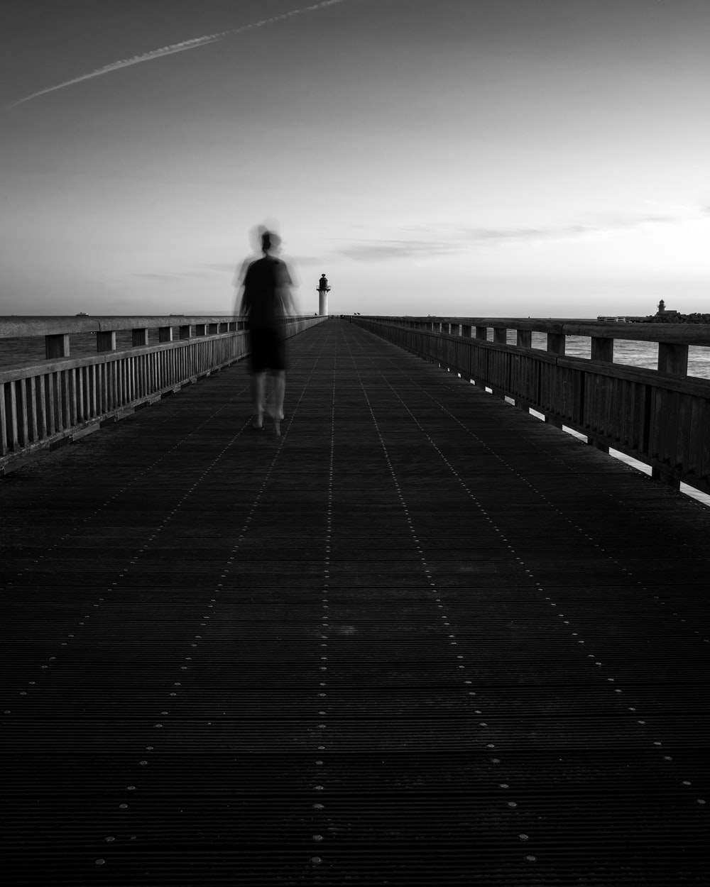 grayscale photo of person walking on wooden bridge