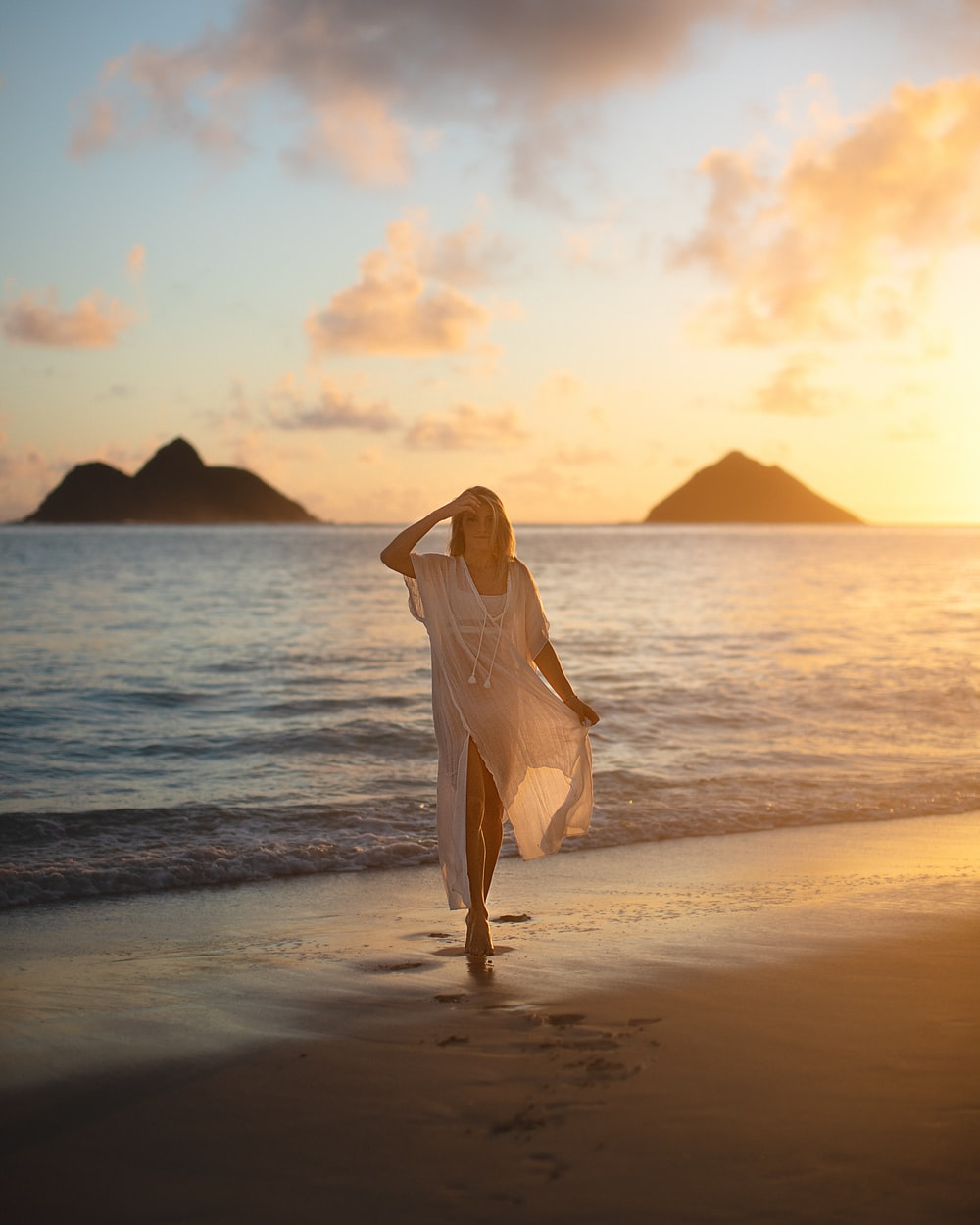woman in white dress standing on beach during sunset