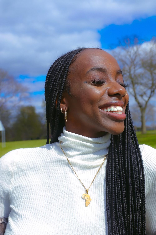 woman in white turtleneck shirt smiling