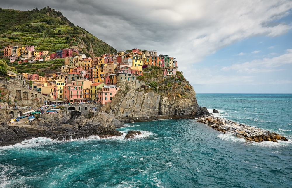 houses on cliff beside sea under blue sky during daytime