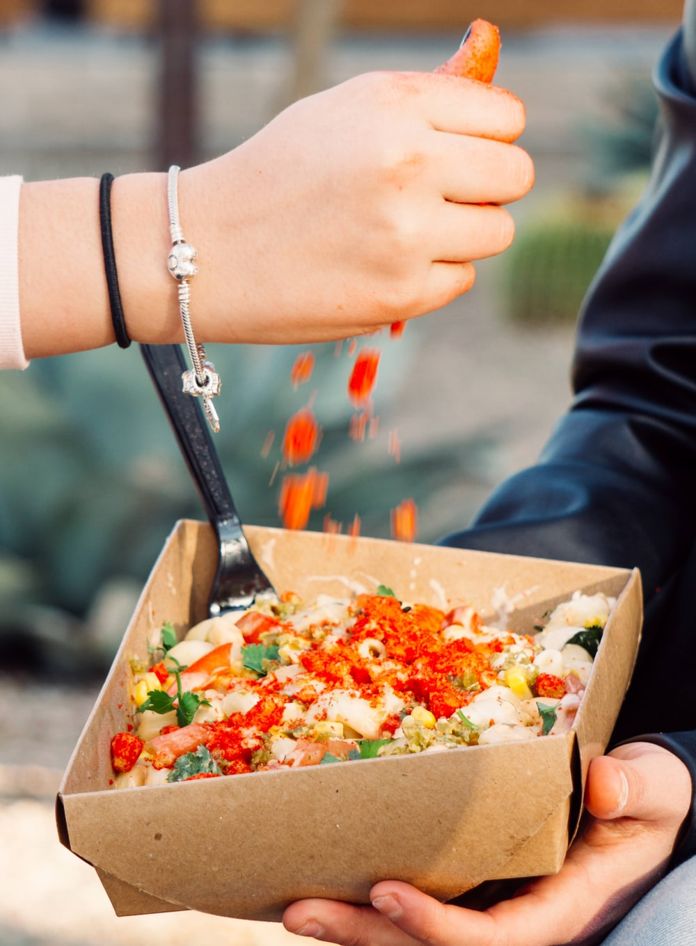 person holding brown box with vegetable salad