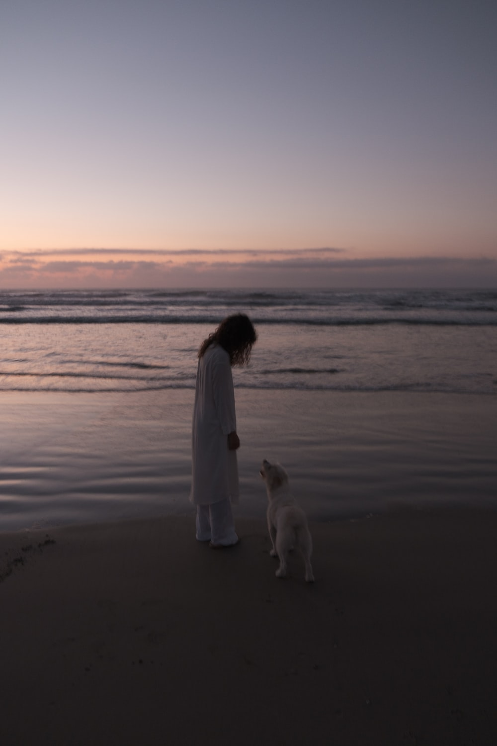 woman in white dress standing on seashore during sunset