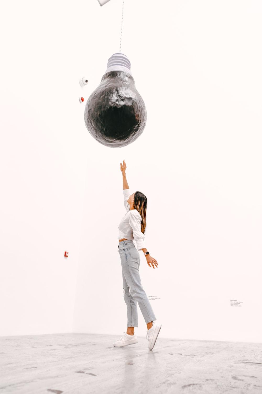 woman in white sleeveless dress standing on globe