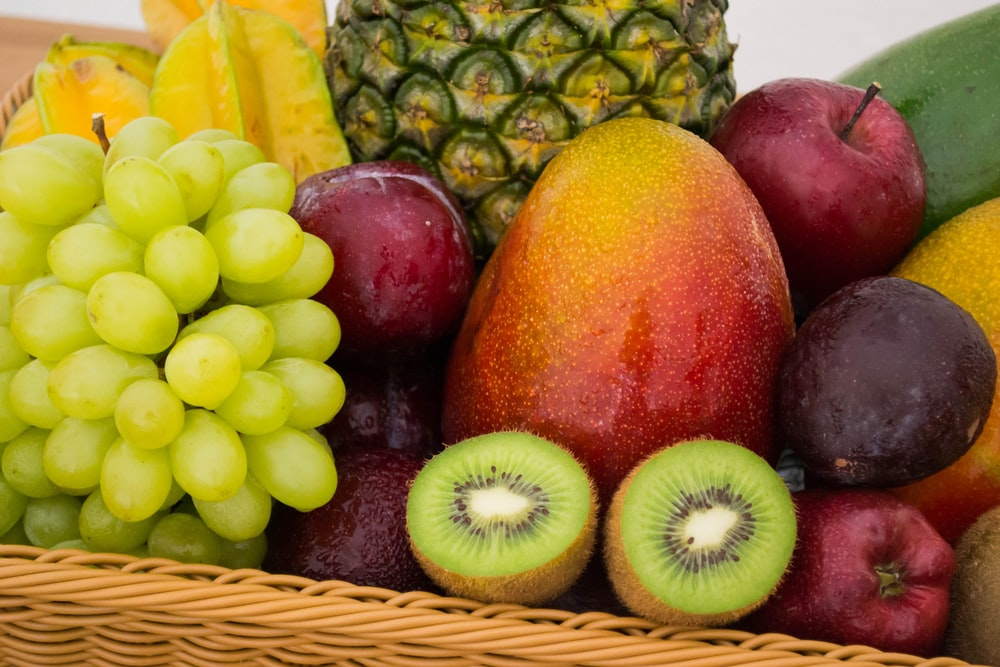 red apple fruit beside green apple and yellow fruit on brown woven basket