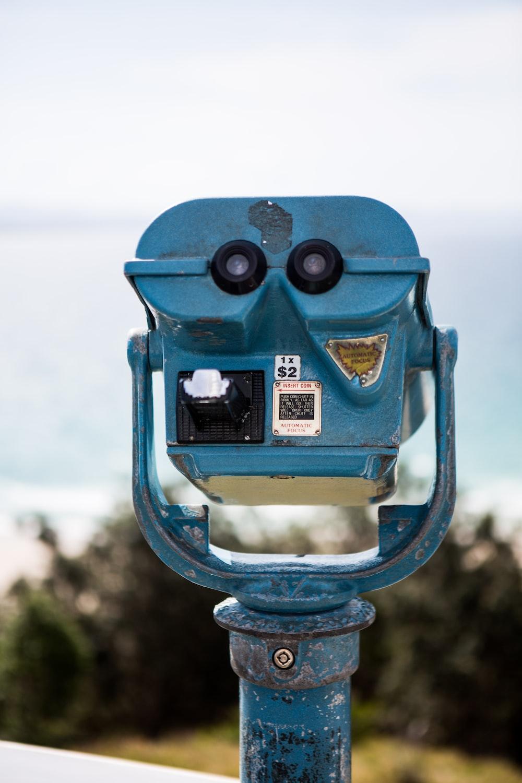 blue binoculars on green metal stand