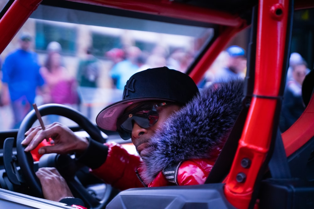 man in red jacket driving car