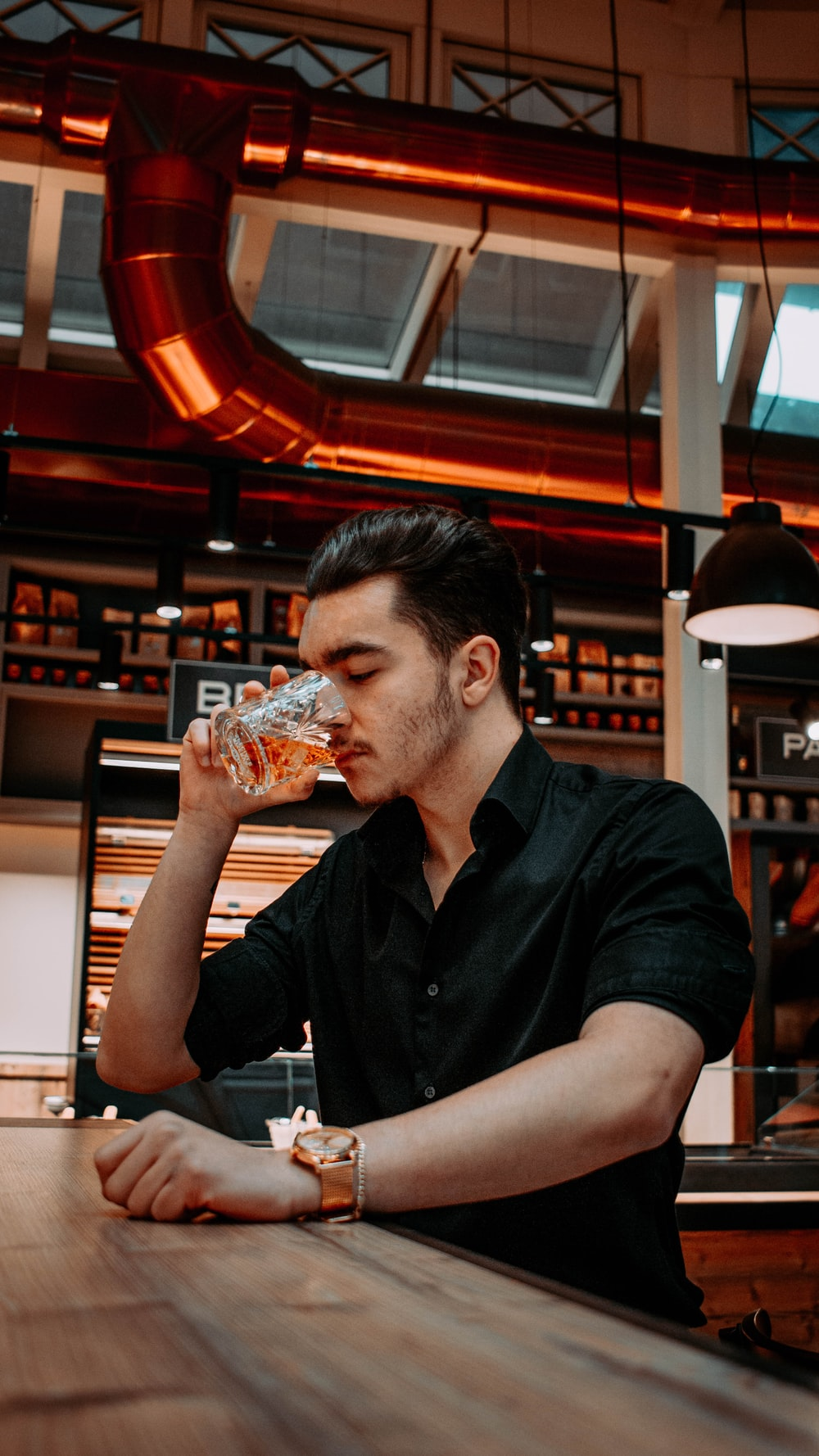 man in black polo shirt drinking from clear drinking glass