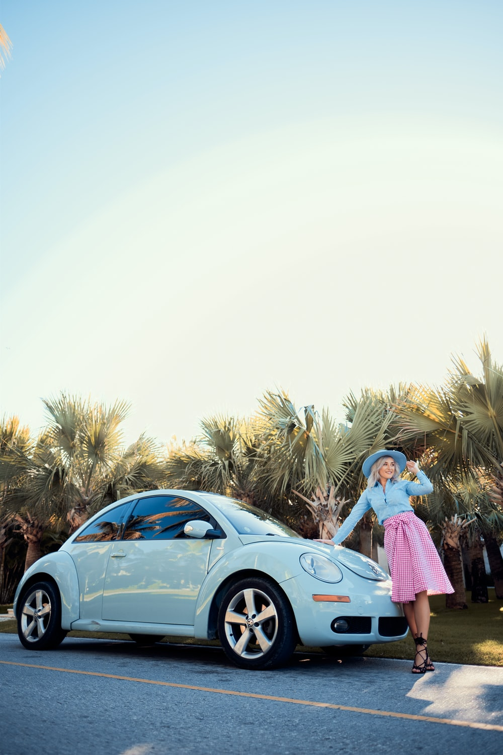woman in pink dress standing beside blue car during daytime