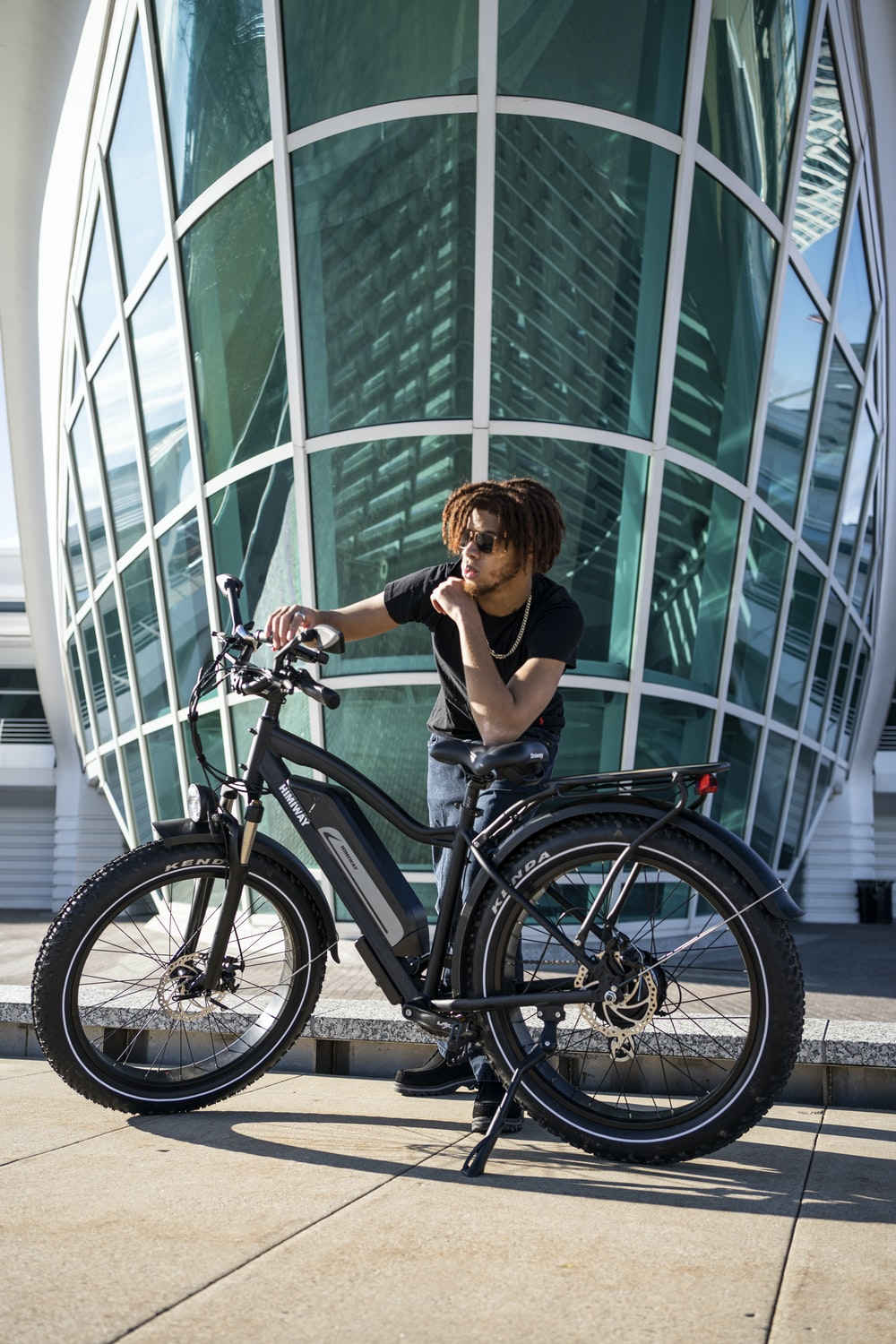 woman in black tank top riding on black bicycle